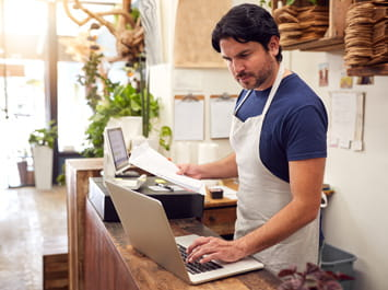 A man standing behind a counter working on a laptop